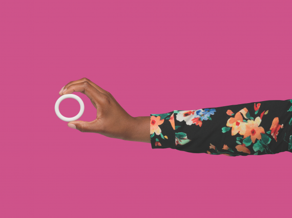 A hand with a floral sleeve holds the Annovera ring against a pink background.
