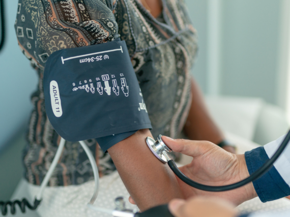 A provider takes a patient's pulse while a blood pressure cuff is strapped to their arm.