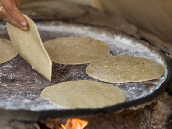 A hand flips a tortilla on a plate over a fire.