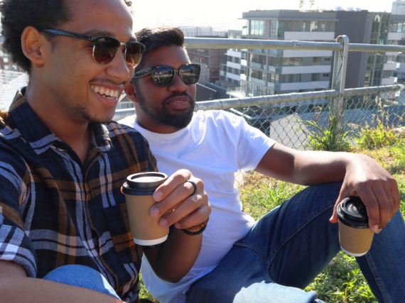 Two Black men relax on a rooftop with coffee.