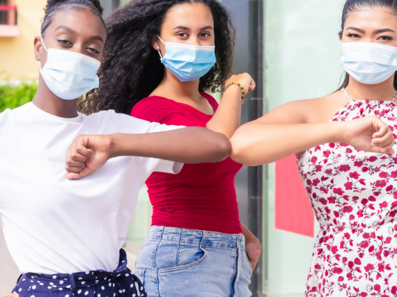 Three young women of color wear masks and touch elbows.