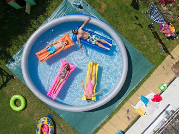 A family of four relaxes on floats in an inflatable pool in the backyard.