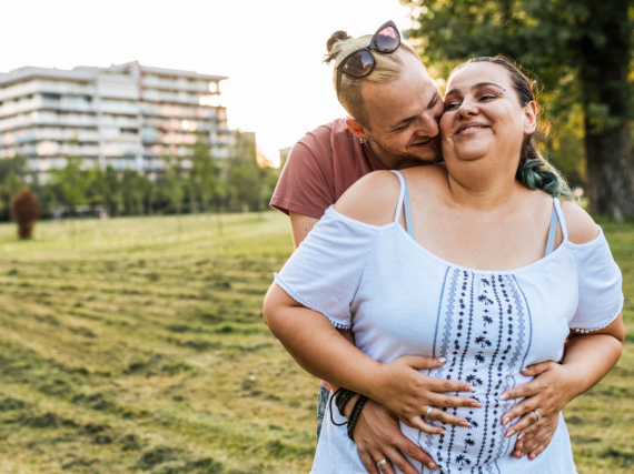 A pregnant woman smiles and is happily hugged by her male partner.