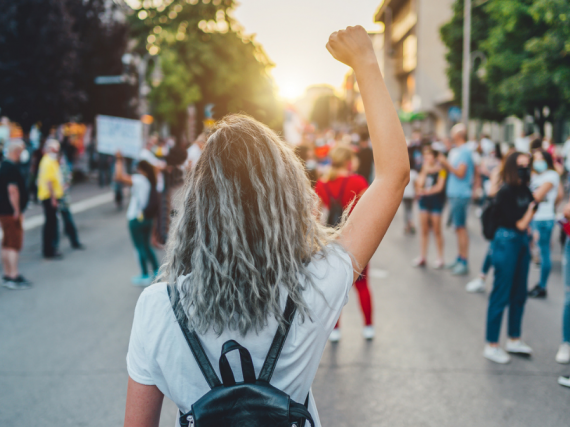 A photo of the back of a young woman at a protest with her fist raised.