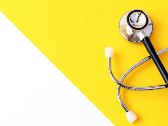 A stethoscope sits on a yellow and white background.