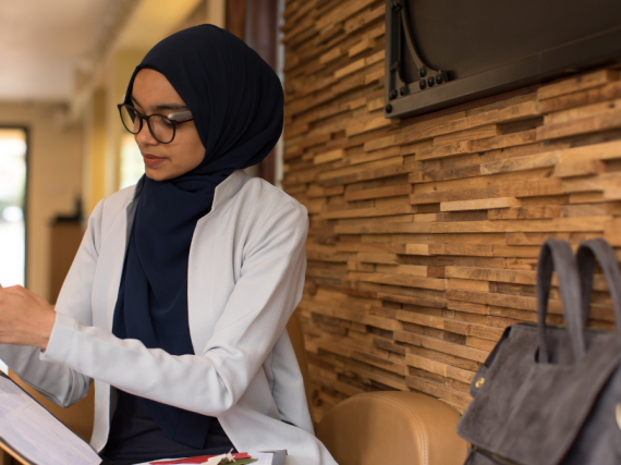 A provider wearing a hijab while sitting on a bench and reviewing information.