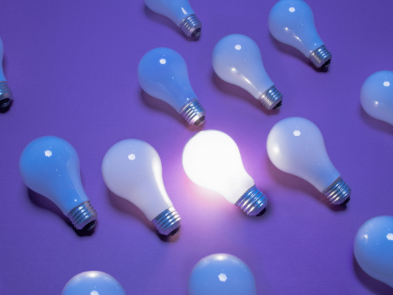 A group of lightbulbs lay on a purple background with only one lit up.