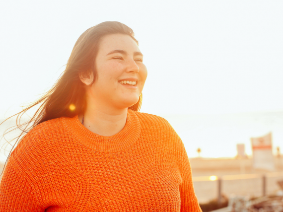 A woman stands on a rooftop at sunset and smiles.