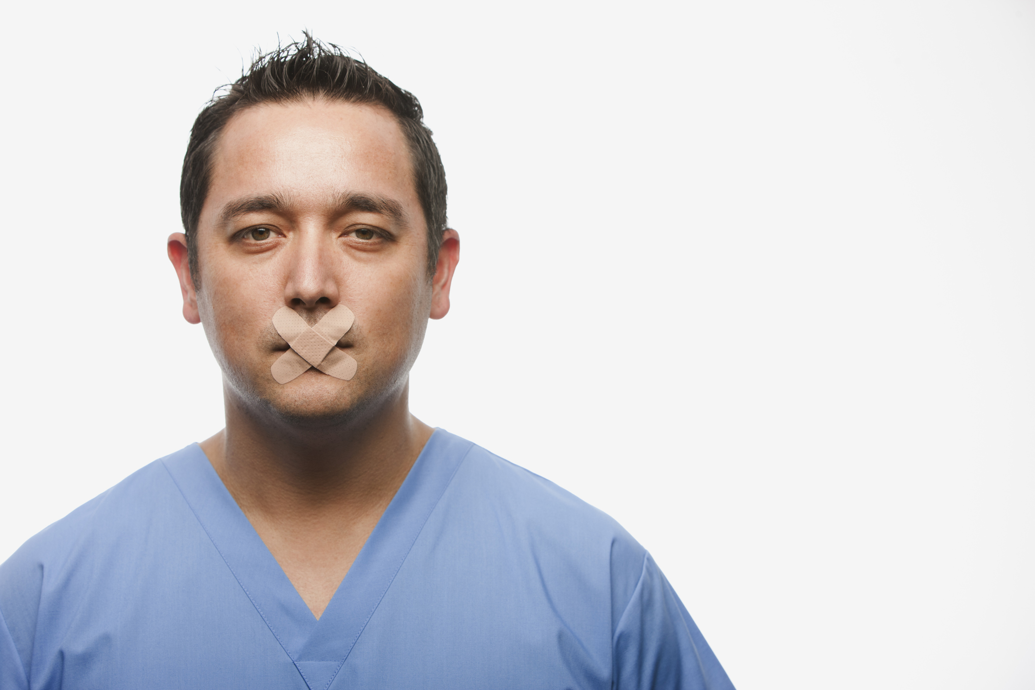 A latino provider with two bandaids covering his mouth