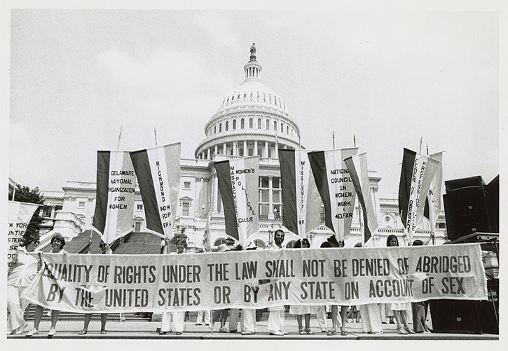 "people standing in front of the United States Capitol with a banner reading ""Equality of rights under the law shall not be denied or abridged by the United States or by any state on account of sex"""