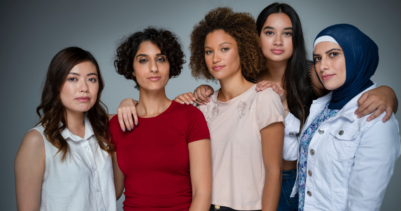 a diverse group of women stands for a portrait